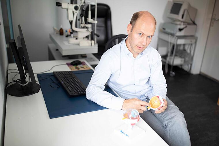 Dr. Groneberg erklärt im Behandlungsraum sitzend am Modellauge das Augenlasern